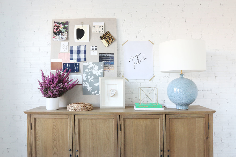 brown cabinet with lavender plant vision board and blue table lamp