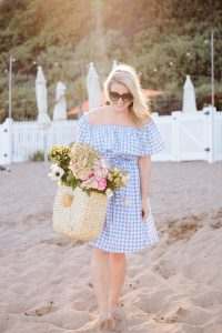 Monika Hibbs holding flowers on the beach in Mailibu