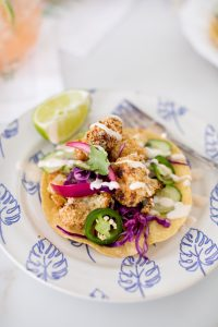 crispy cauliflower tostada on a palm plate