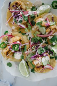 four crispy cauliflower tostadas on a large white dish