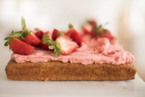 cake topped with icing and cut strawberries