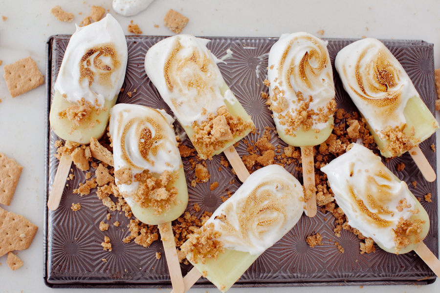 seven lemon meringue popsicles on a pan