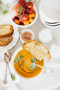 bowl of soup with a slice of toast on the side