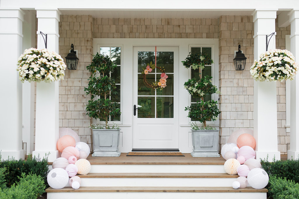 paper floral wreath on and paper lanterns leading up to the door