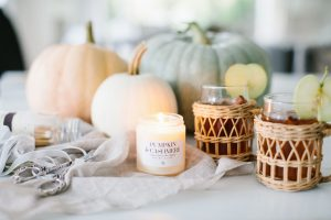 pumpkins, burning candle and apple cider