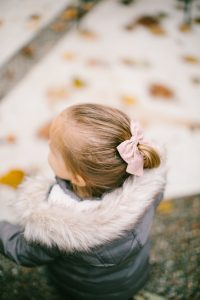 Little girl playing in winter coat and pink bow