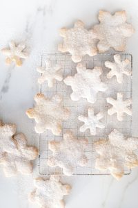 small and large snowflake cookies on marble countertop
