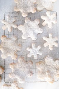 different sized snowflake cookies on cooling rack dusted with icing sugar