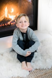 little boy sitting by fire