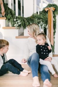 mom and son and daughter sitting on floor christmas time