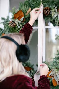 hanging wreath outside tying bow with faux fur pom pom's