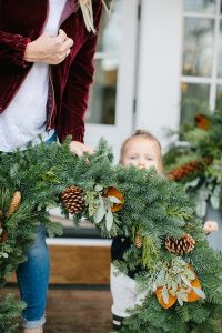 toddler girl outside with large wreath