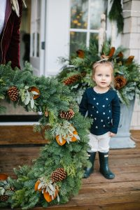 little girl outside but large christmas wreath