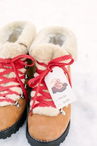 Boots in snow with red laces and matching gift tag