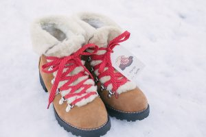 Boots in snow with red laces and gift tag attached