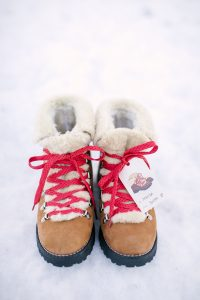 boots in snow with red laces and gift tag