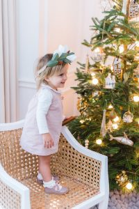 little girl on dinning chair, tree behind