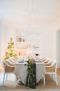 white dinning room set up with christmas table