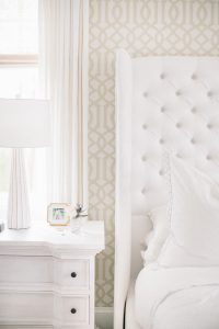 white tufted headboard, neutral wallpaper, bedside table