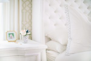 bedside table wit bud vase and white linens