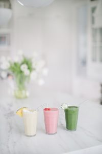 smoothies on counter red, tropical and green flowers in background