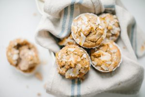 close up of banana muffins in tin with a linen napkin