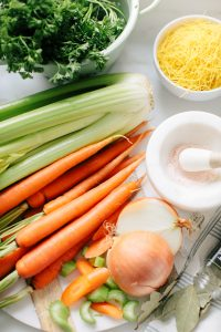 carrots celery and onions on board, with other chicken noodle soup ingredients