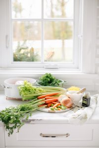 ingredients on counter for chicken noodle soup, window in background