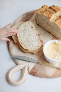 slices of bread on french country wooden cutting board, butter in a dish