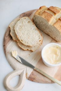 country style bread on wooden board with butter in dish