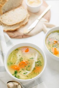 two bowls of chicken noodle soup with bread on cutting board