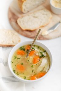 bowl of chicken soup with with bread on the side on wooden cutting board