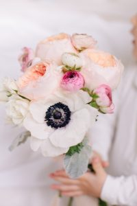 little girl holding bouquet of flowers