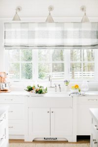airy white kitchen window sink with buffalo check roman blind