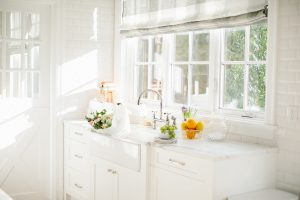 airy white kitchen with florals and fruit on the counter