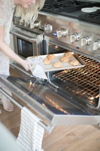 women removing cookies from oven