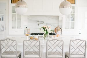 white kitchen with large marble island and pendant lighting