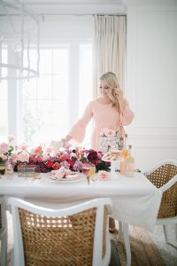 women in pink dress setting beautiful valentines table