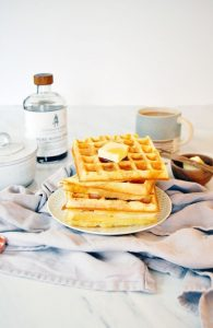 waffels staked with maple syrup on the side