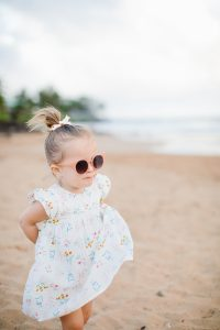 little girl on beach in dress, sunglasses and hair in bow
