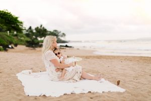 mom cuddling with little girl on beach at sunset