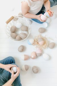 toddler girl with paper mâché easter eggs