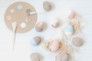 flat lay paper painted easter eggs and raffia