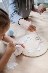 toddlers painting easter eggs with pain brushes