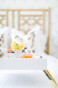 Grapefruit and florals on tray in bed