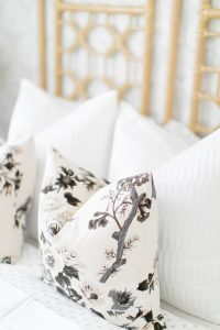 light grey and black floral pillows on bed