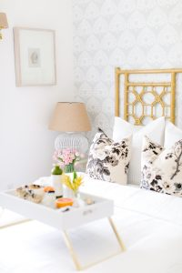 White airy guest room with breakfast in bed