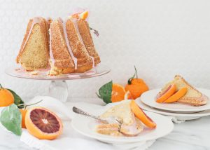 citrus bundt cake on cake stand with sliced cake on plates