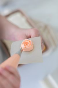 piping butter cream rose on flower nail