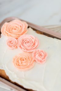 pink buttercream rose on white icing